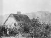 1892 Photo prise depuis la route de Boeschepe, d\'une maison au toit de chaume.  Au loin en haut, l\'abbaye.